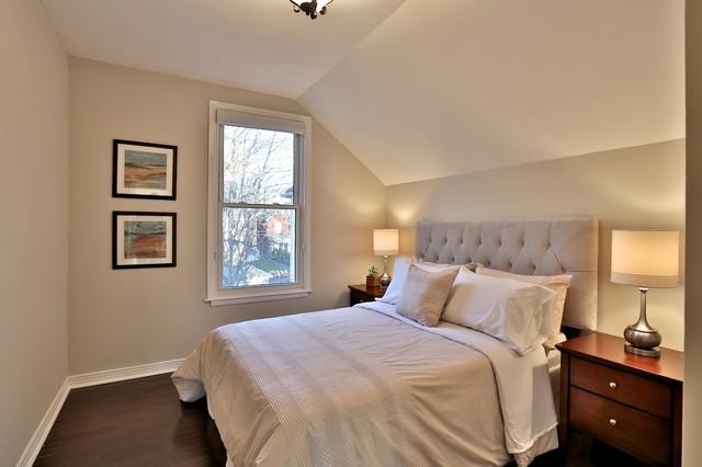 Modelo de habitación de invitados clásica renovada, sin chimenea, con paredes beige y suelo de madera en tonos medios