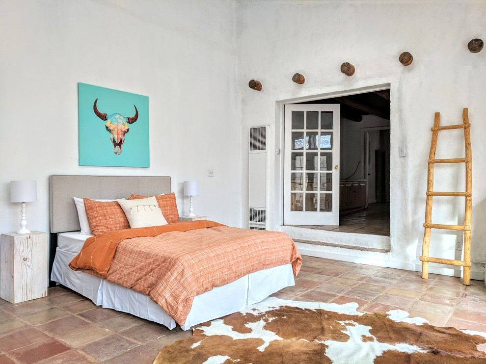Inspiration for a large southwestern master terra-cotta tile and beige floor bedroom remodel in Other with white walls, a corner fireplace and a concrete fireplace