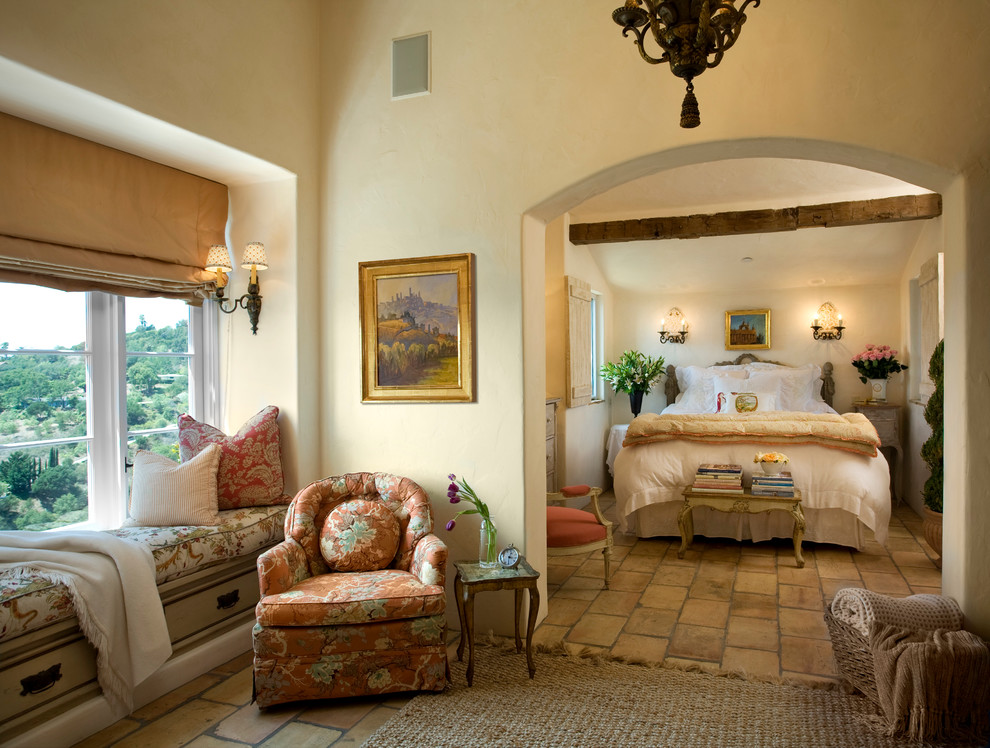 Example of a tuscan brown floor bedroom design in Santa Barbara with beige walls