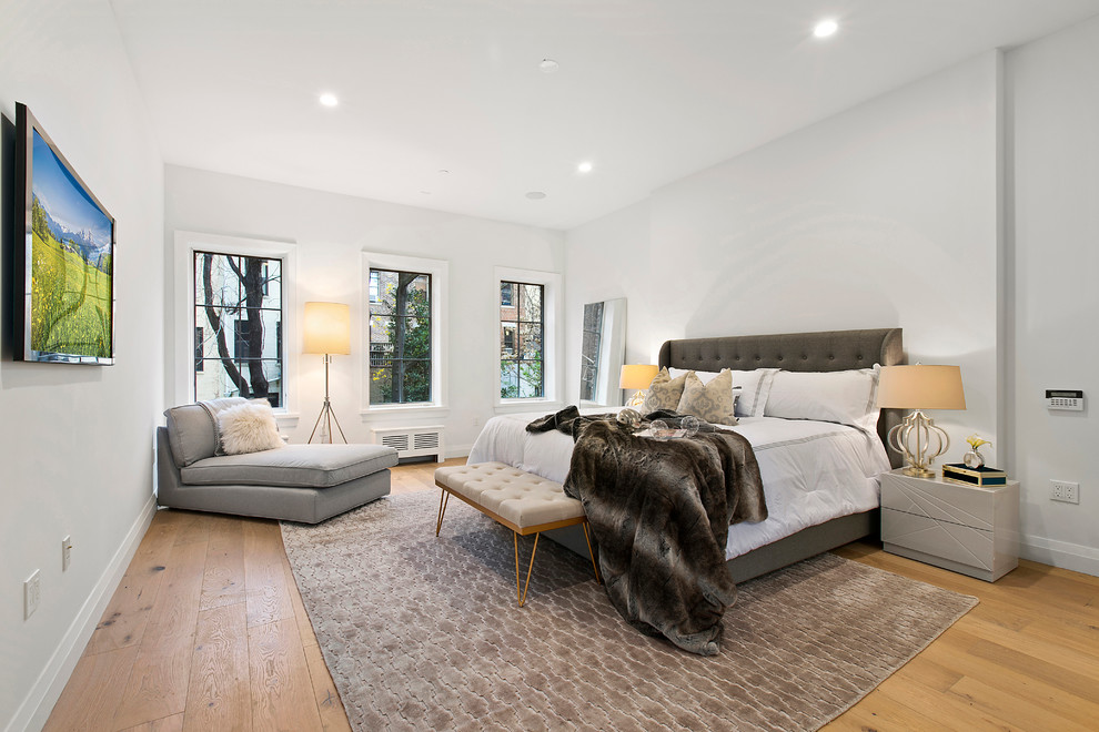 Example of a large transitional master light wood floor and brown floor bedroom design in New York with gray walls and no fireplace