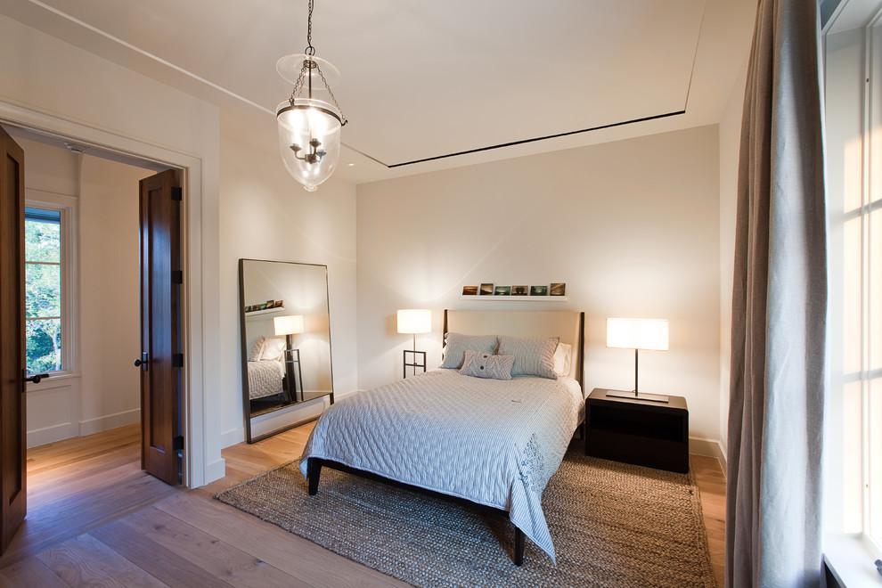 Elegant medium tone wood floor bedroom photo in Austin with beige walls