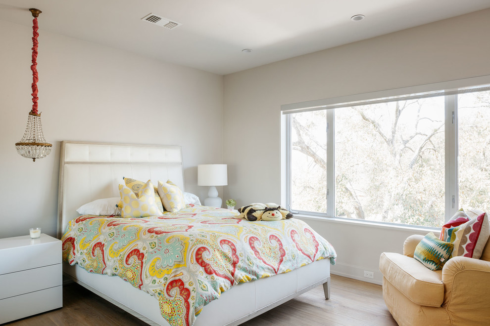 Example of a trendy light wood floor bedroom design in Houston with white walls