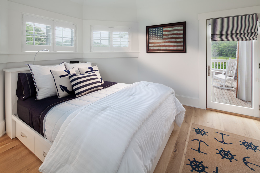 Example of a beach style medium tone wood floor bedroom design in DC Metro with white walls