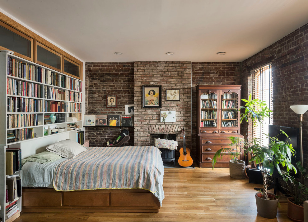 Bedroom - small industrial loft-style light wood floor bedroom idea in New York with a wood stove and a brick fireplace