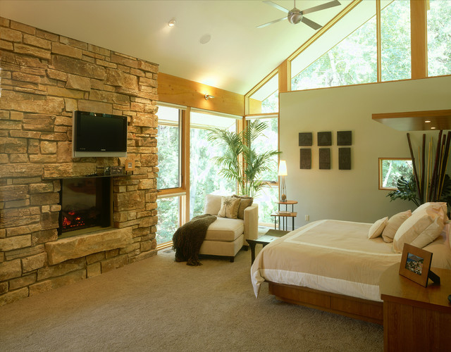 vaulted master bedroom with stone fireplace and raised hearth contemporary bedroom