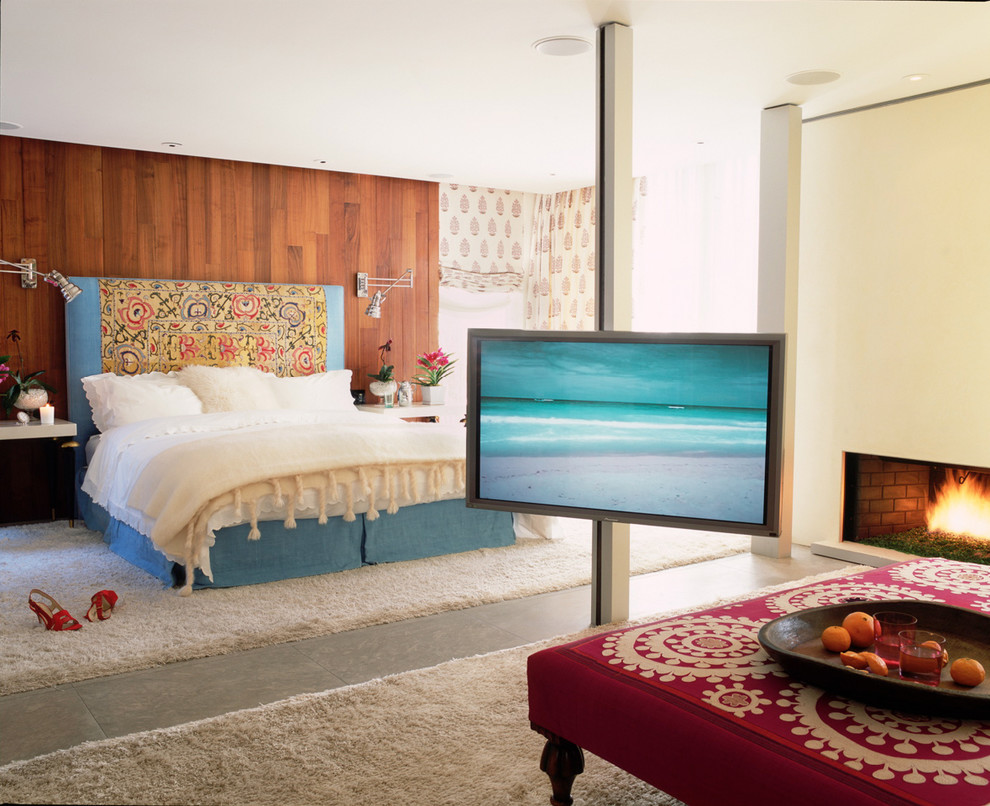 Example of a large trendy master concrete floor bedroom design in Los Angeles with beige walls, a standard fireplace and a plaster fireplace