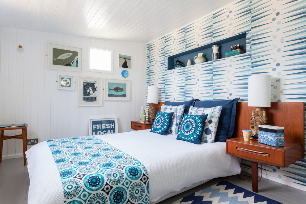 Beach style painted wood floor bedroom photo in London with white walls