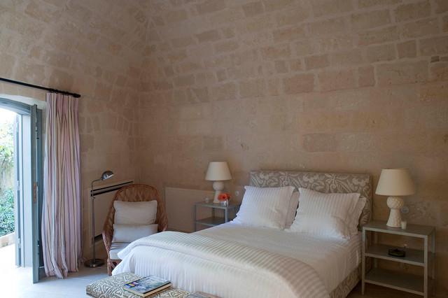 Создайте стильный интерьер: маленькая спальня с бежевыми стенами, полом из известняка, камином и фасадом камина из камня для гостей - последний тренд