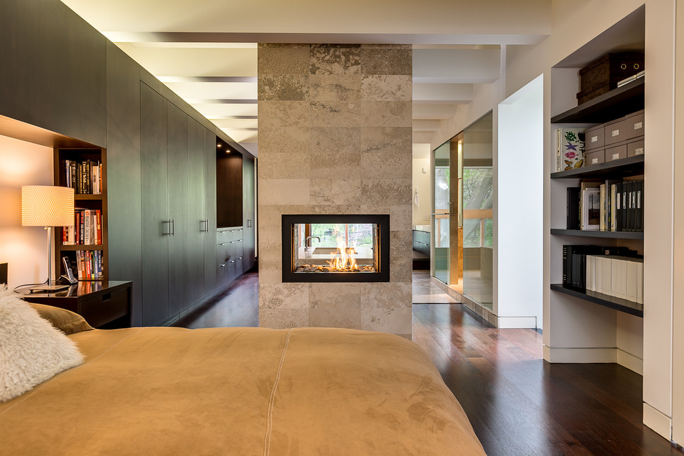 Example of a trendy bedroom design in Toronto with a tile fireplace and a two-sided fireplace