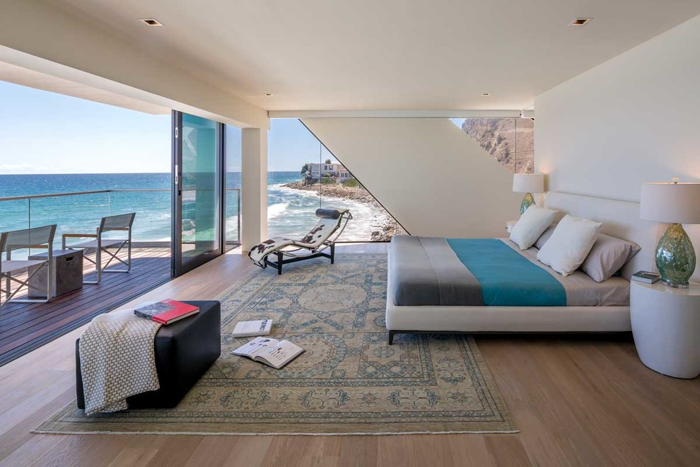 Large trendy master medium tone wood floor bedroom photo in Los Angeles with white walls and no fireplace