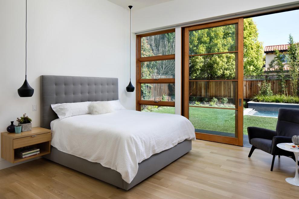 Example of a trendy light wood floor and beige floor bedroom design in San Francisco with white walls