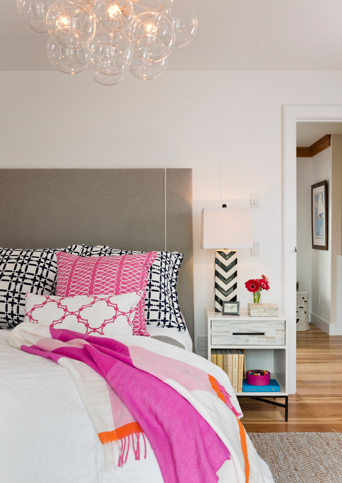 Inspiration for a timeless medium tone wood floor bedroom remodel in Providence with white walls