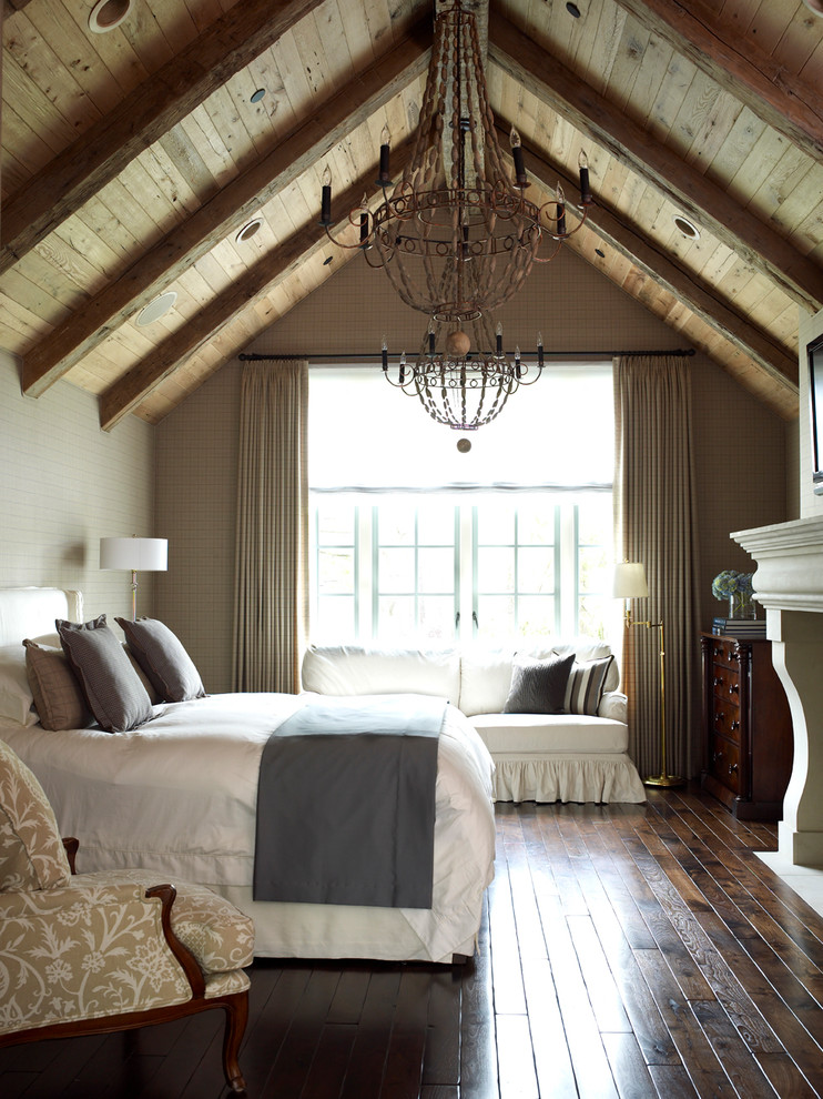 Bedroom - large country dark wood floor bedroom idea in Houston with gray walls, a standard fireplace and a stone fireplace