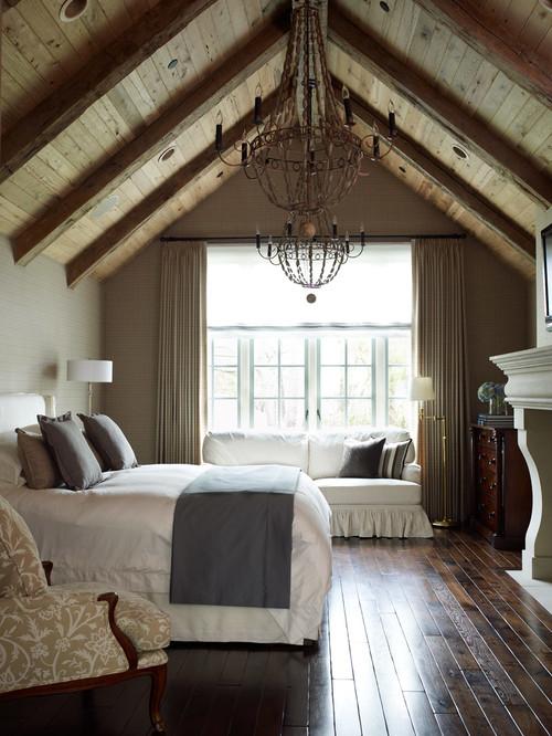 Классическая спальня в коттедже с камином с деревянным потолком
