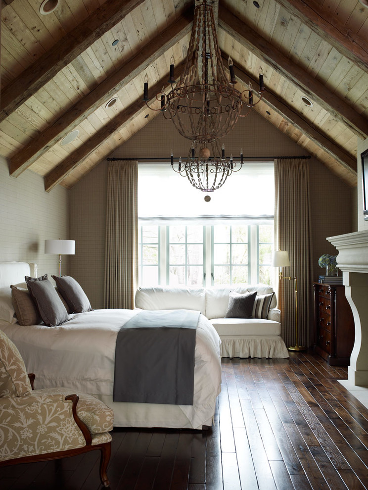 Example of a classic dark wood floor bedroom design in Houston with beige walls and a standard fireplace