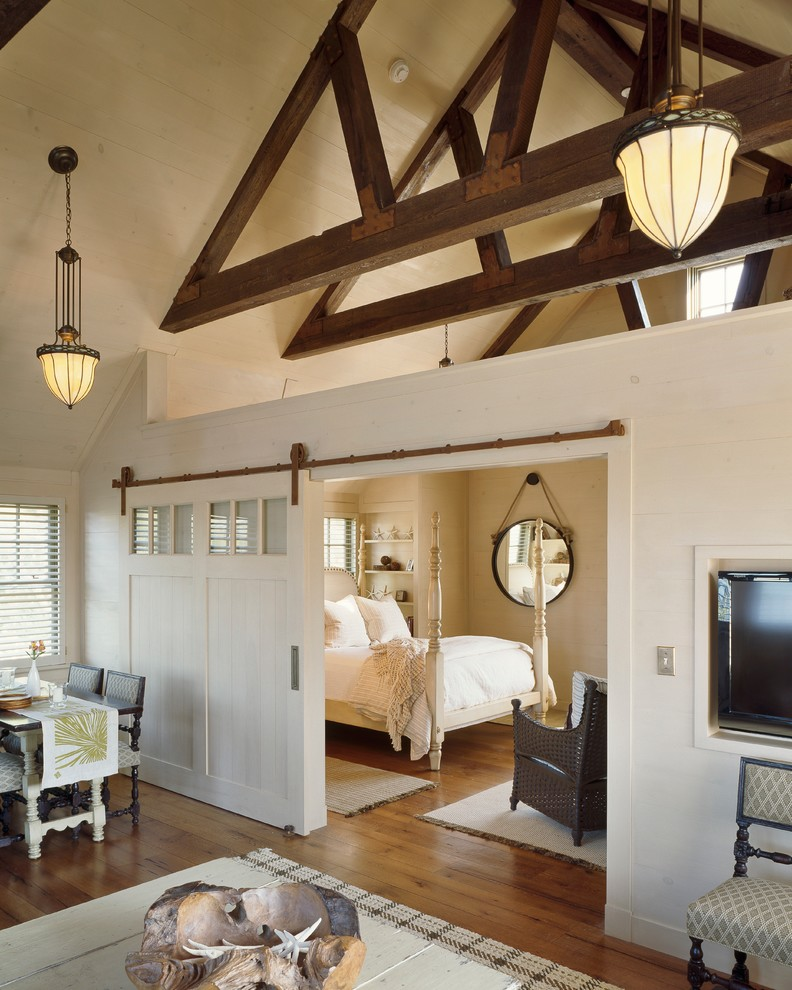 Example of a mid-sized farmhouse medium tone wood floor bedroom design in Boston with white walls