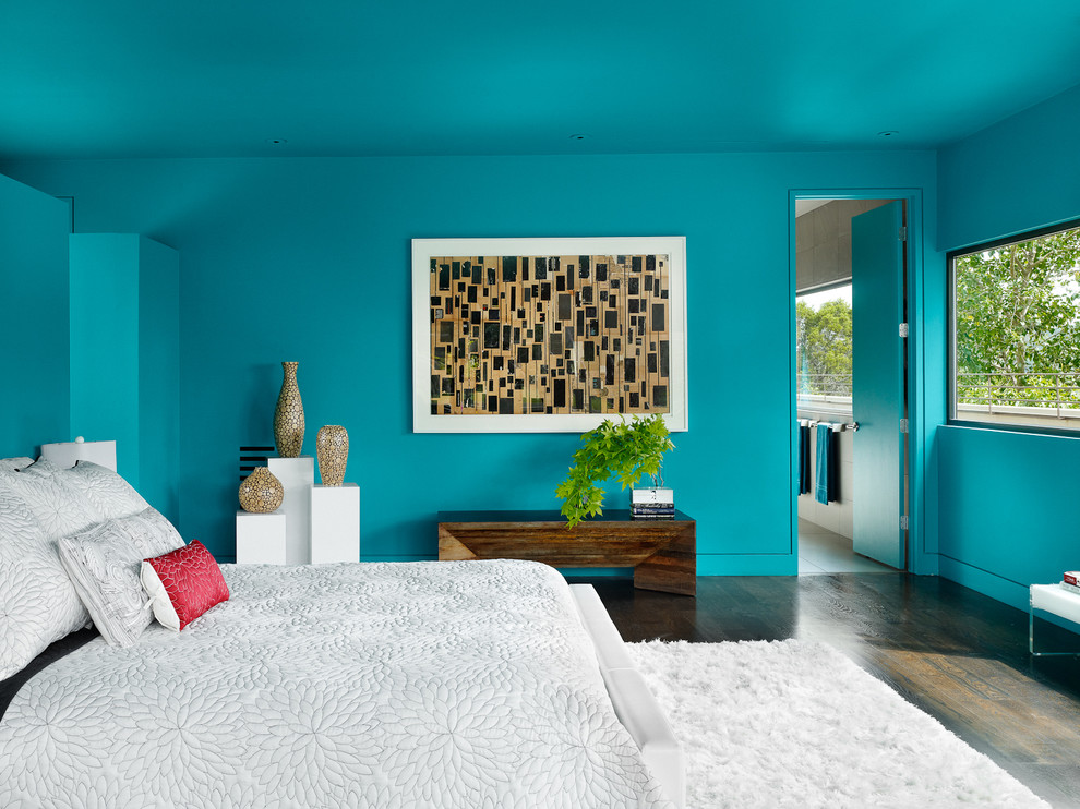 Example of a trendy master dark wood floor bedroom design in Austin with blue walls and no fireplace