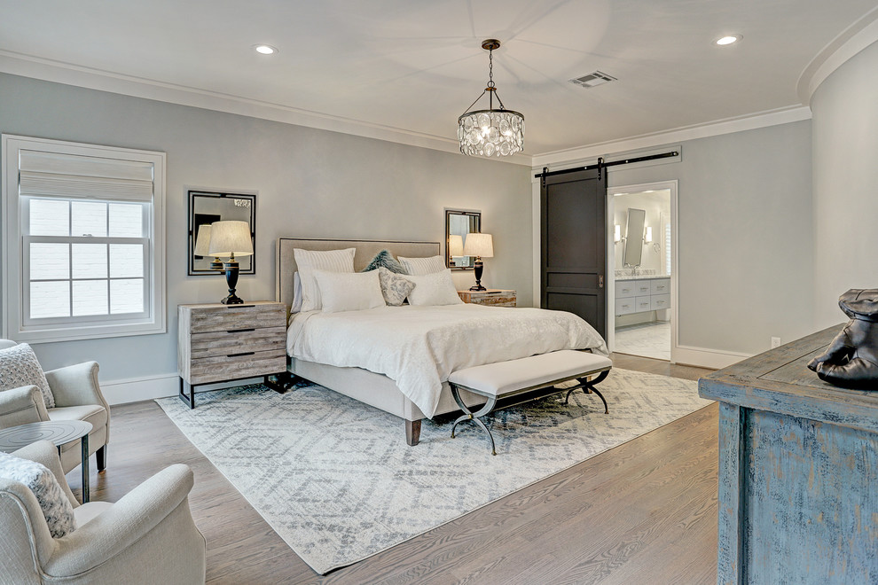 Mid-sized transitional master light wood floor and brown floor bedroom photo in Houston with gray walls