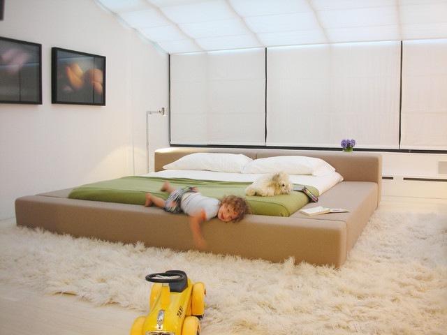 Example of a danish light wood floor bedroom design in New York with white  walls