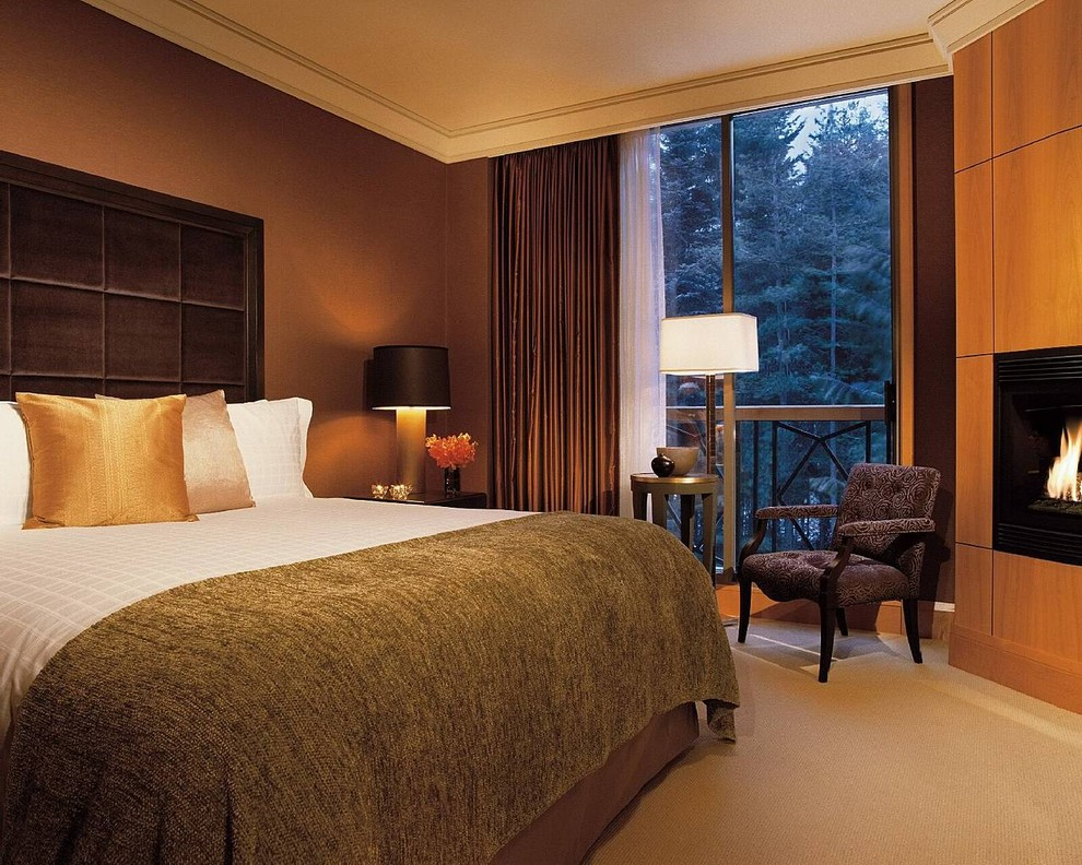 Trendy bedroom photo in Vancouver with brown walls and a wood fireplace surround