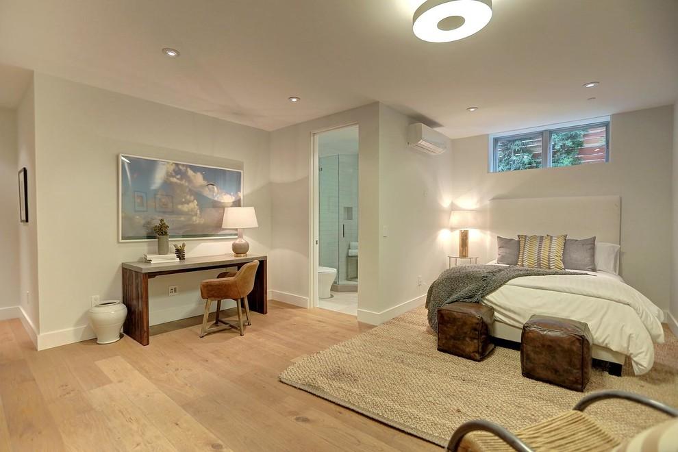 Mid-sized minimalist guest medium tone wood floor bedroom photo in Los Angeles with gray walls