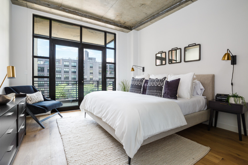 Inspiration for a mid-sized contemporary guest light wood floor and brown floor bedroom remodel in New York with white walls