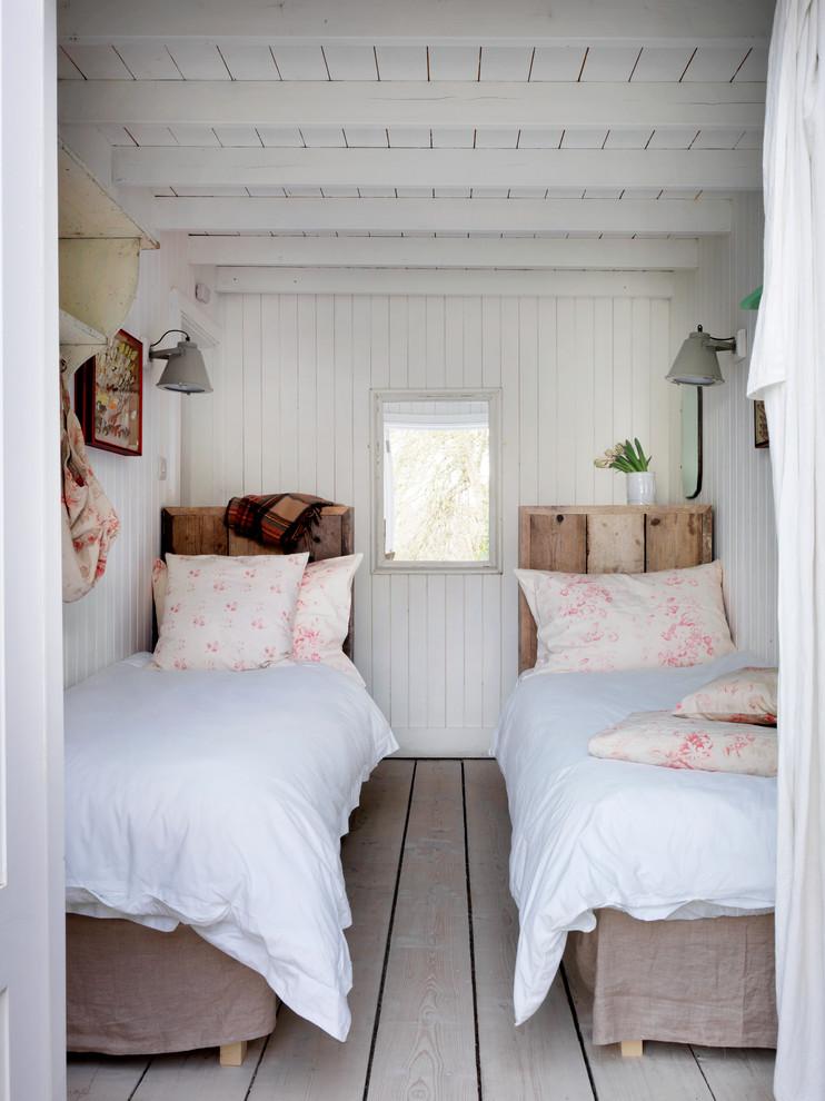 Bedroom - beach style light wood floor bedroom idea in London with white walls