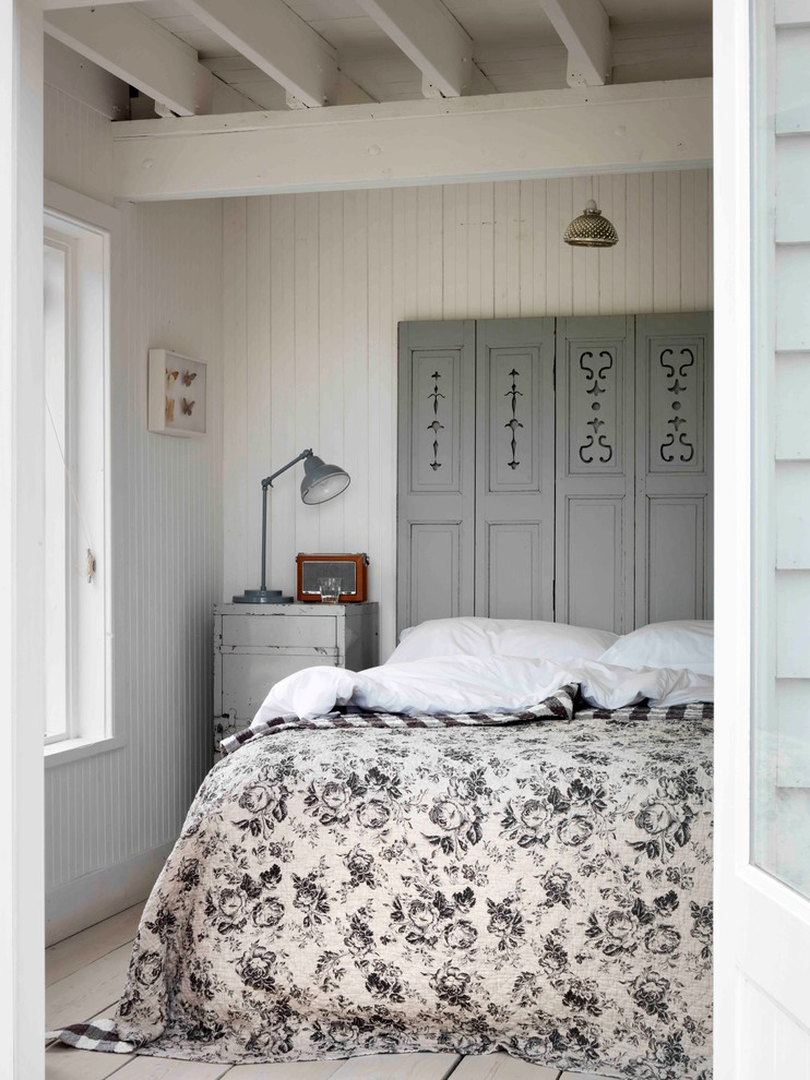Cottage chic light wood floor bedroom photo in London with white walls