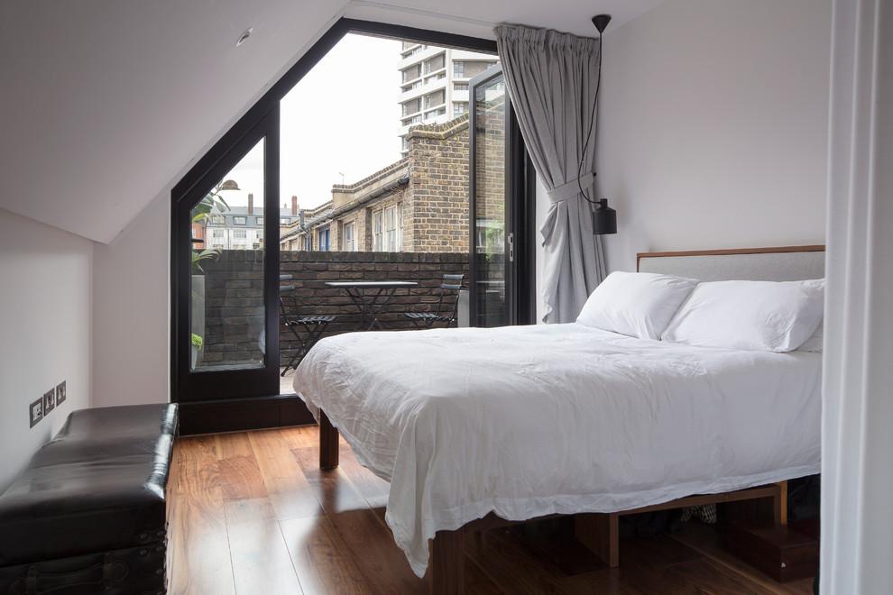 Urban medium tone wood floor bedroom photo in London with white walls