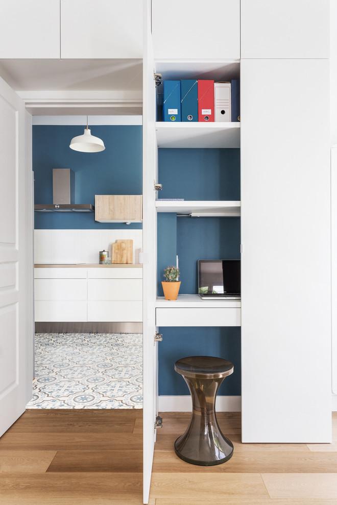 Aménagement d'un petit bureau scandinave avec un mur bleu, un sol en bois brun, aucune cheminée et un bureau intégré.