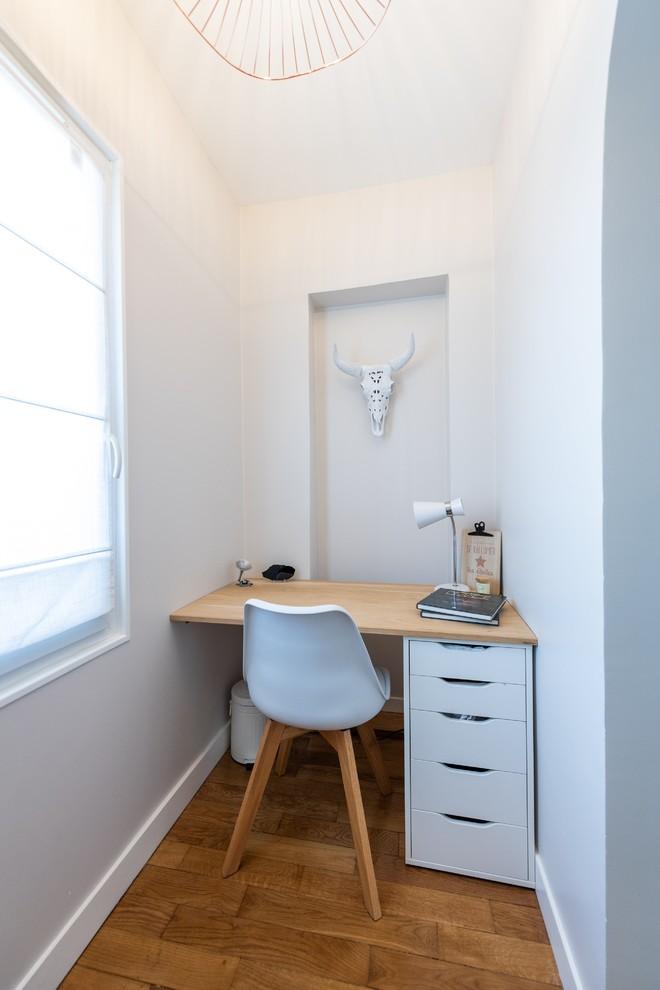 Idée de décoration pour un bureau nordique avec un mur blanc, un sol en bois brun, un bureau intégré et un sol marron.