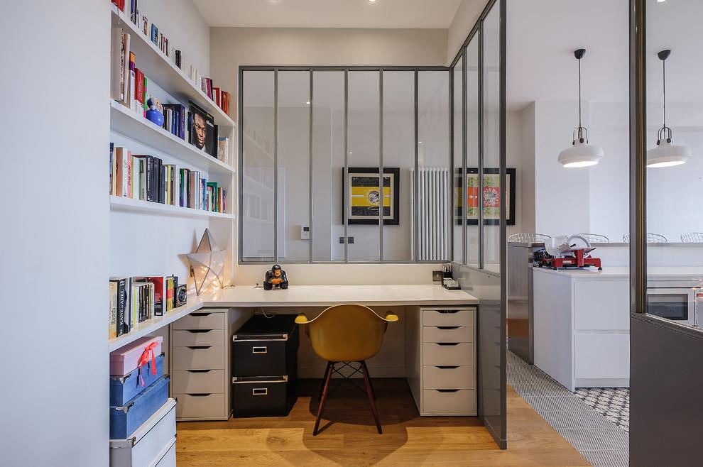 Réalisation d'un bureau design avec un mur blanc, un sol en bois brun et un bureau intégré.
