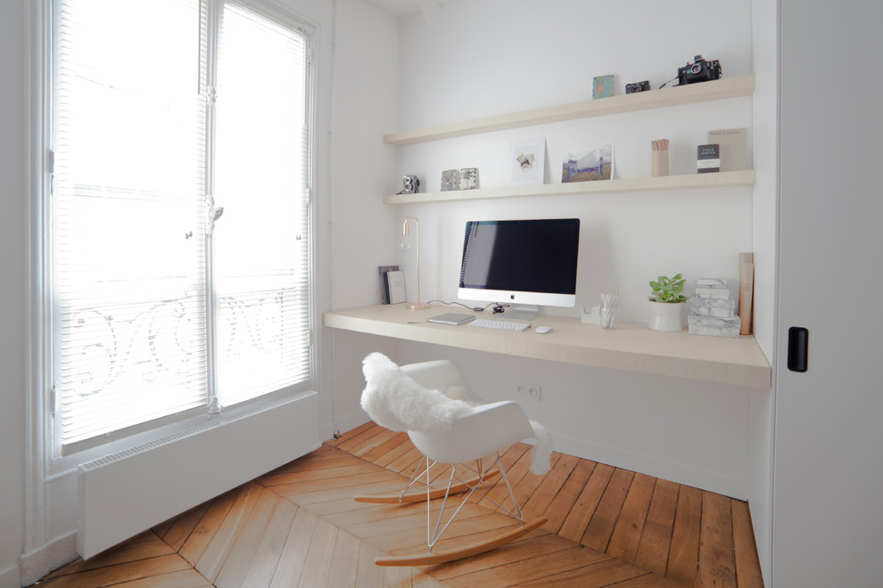 Inspiration for a mid-sized scandinavian built-in desk medium tone wood floor study room remodel in Other with white walls and no fireplace