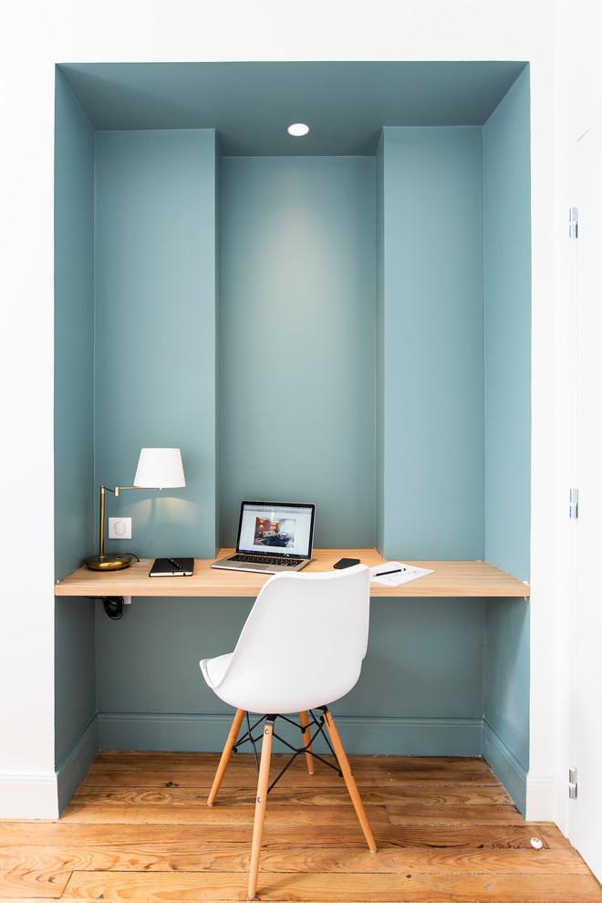 Ejemplo de despacho contemporáneo con paredes azules, suelo de madera en tonos medios, escritorio empotrado y suelo marrón