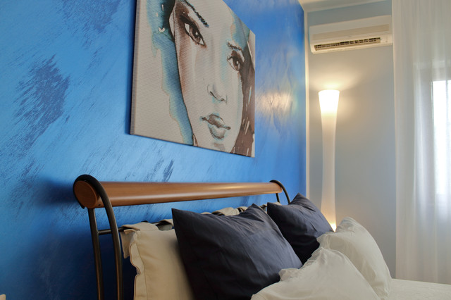 Esempio di una grande camera matrimoniale contemporanea con pareti blu e pavimento in gres porcellanato
