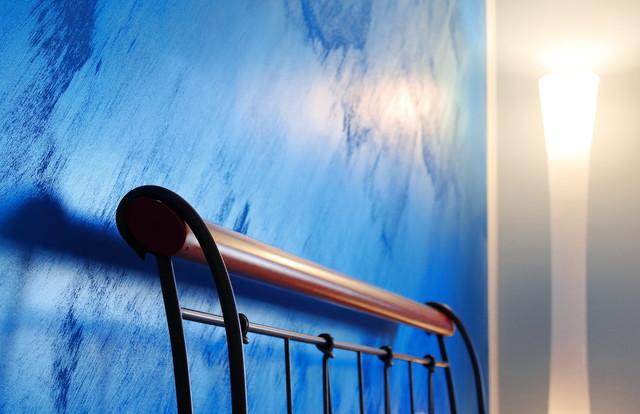 Immagine di una grande camera matrimoniale contemporanea con pareti blu, pavimento in gres porcellanato e pavimento multicolore