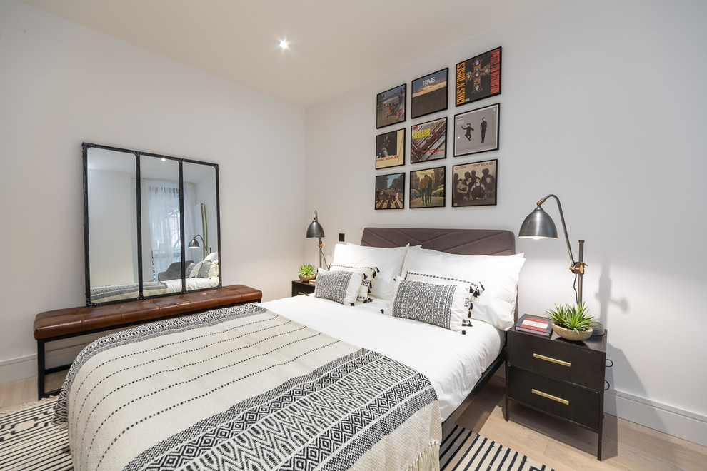 Inspiration for a scandinavian light wood floor and beige floor bedroom remodel in London with white walls and no fireplace