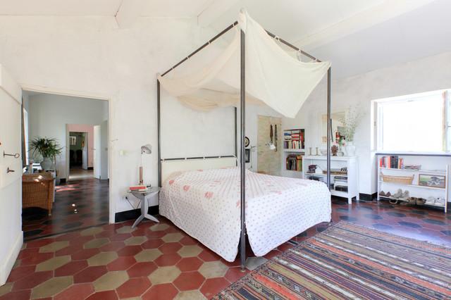 Ispirazione per una camera matrimoniale mediterranea con pareti bianche, pavimento in cemento e pavimento multicolore