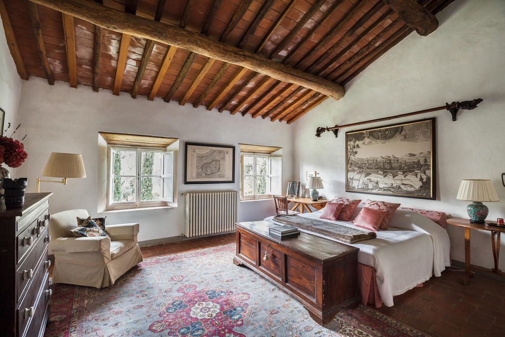 Large farmhouse master terra-cotta floor and red floor bedroom photo in Florence with white walls