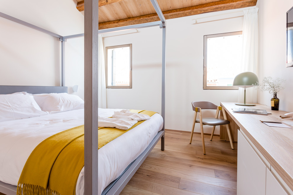 Inspiration for a mediterranean light wood floor and brown floor bedroom remodel in Other with white walls