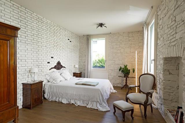 Foto di una grande camera matrimoniale mediterranea con pareti bianche, pavimento in legno massello medio e nessun camino