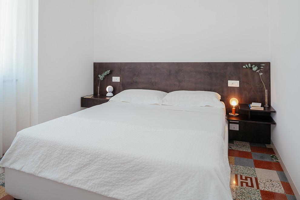 Immagine di una camera padronale contemporanea con pareti bianche e pavimento multicolore