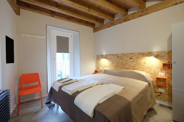 Esempio di una camera matrimoniale design con pareti beige, pavimento in gres porcellanato e pavimento grigio