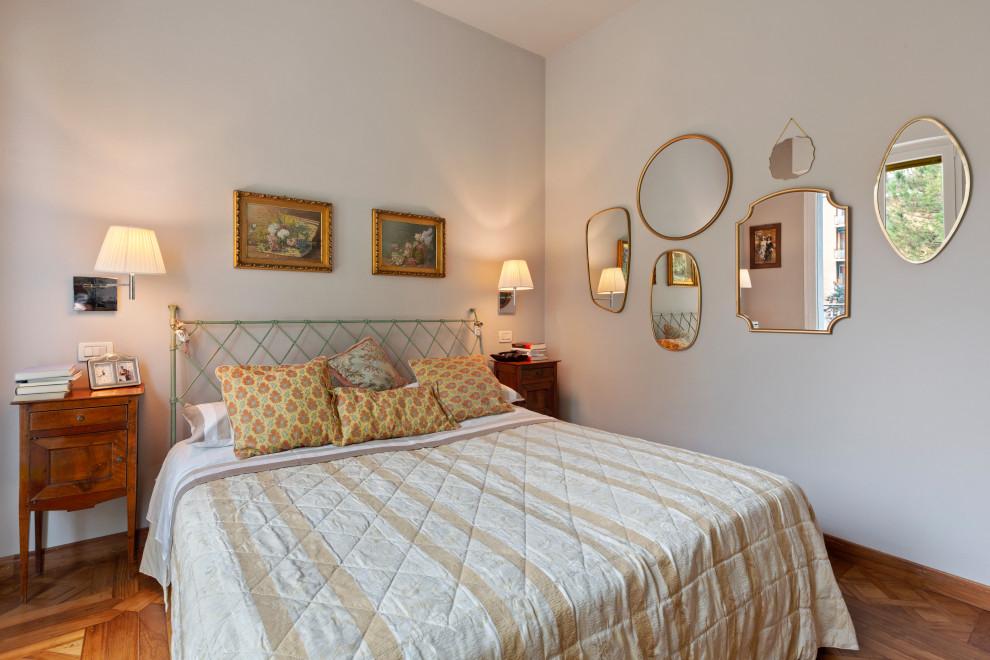 Ispirazione per una camera da letto mediterranea con pareti grigie, pavimento in legno massello medio e pavimento marrone