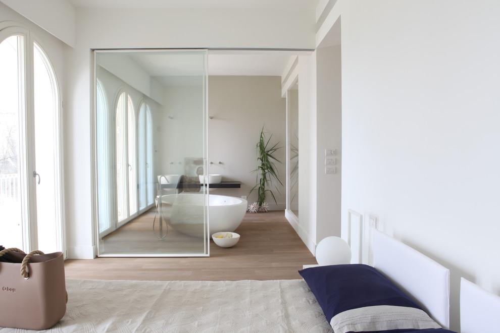 Immagine di una grande camera padronale al mare con pareti bianche e parquet chiaro