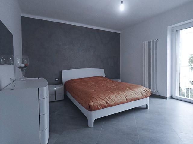 Esempio di una camera matrimoniale minimal di medie dimensioni con pareti bianche, pavimento in gres porcellanato, nessun camino e pavimento grigio