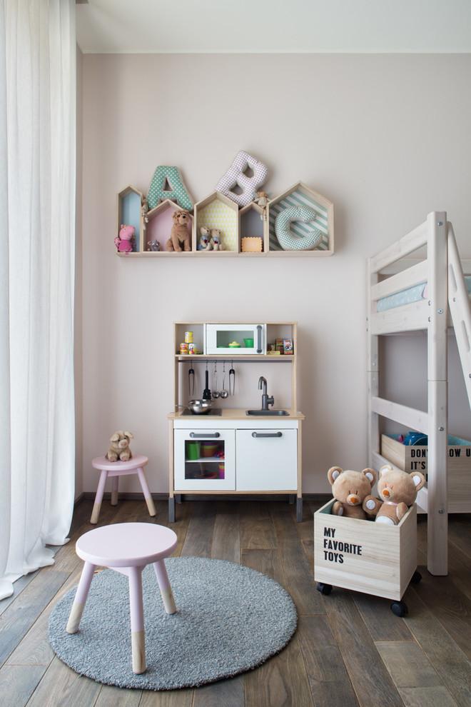 Mid-sized danish gender-neutral dark wood floor kids' room photo in Milan with pink walls