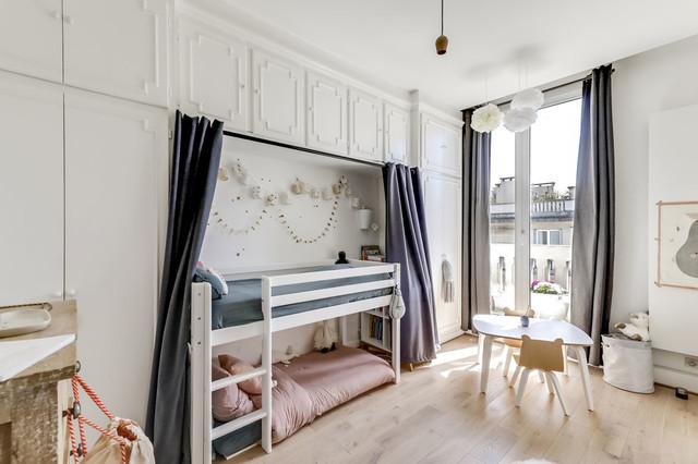 Idée de décoration pour une chambre d'enfant de 4 à 10 ans nordique de taille moyenne avec un mur blanc, un sol en bois clair et un sol beige.