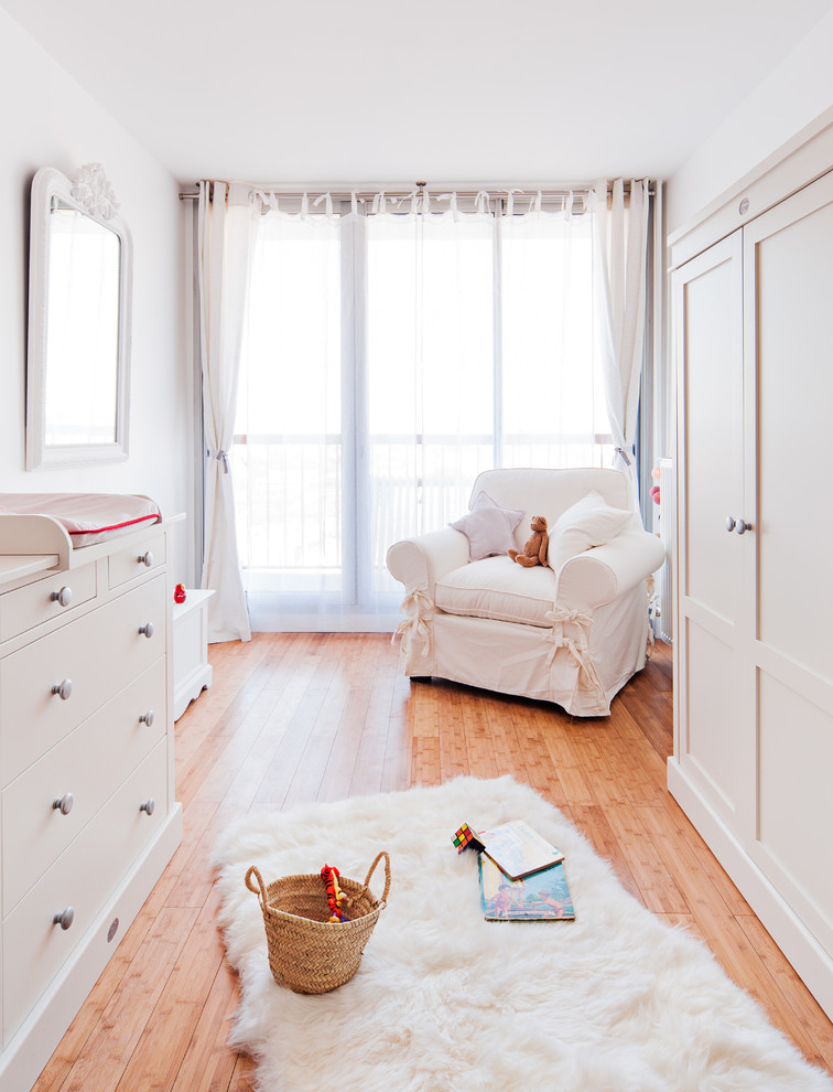 Inspiration for a large cottage gender-neutral light wood floor nursery remodel in Paris with white walls
