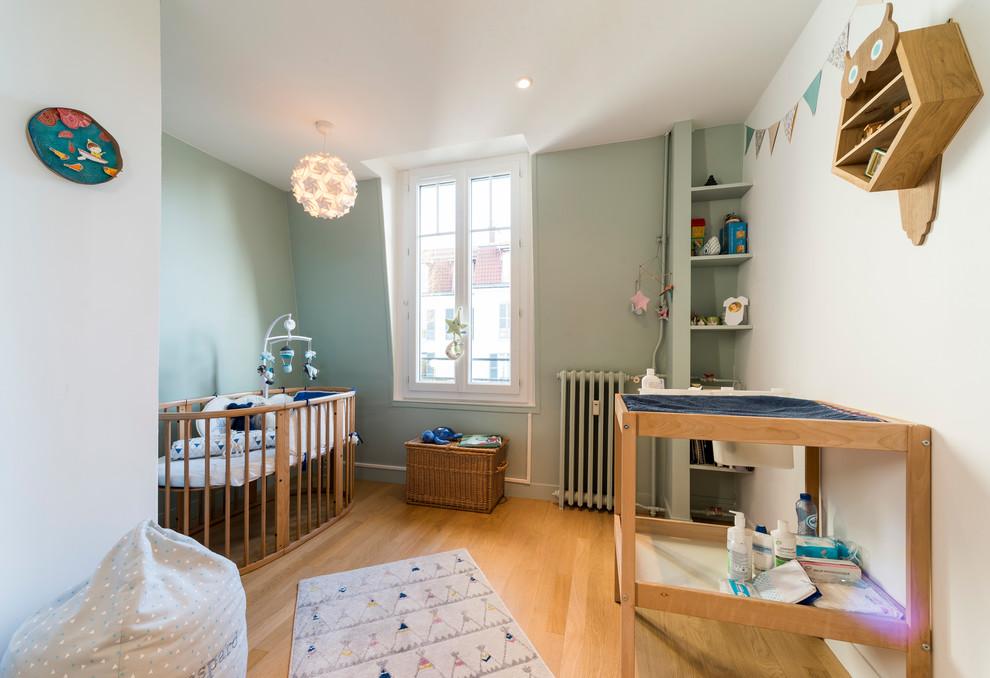 Idée de décoration pour une chambre de bébé tradition avec un mur vert, un sol en bois clair et un sol beige.